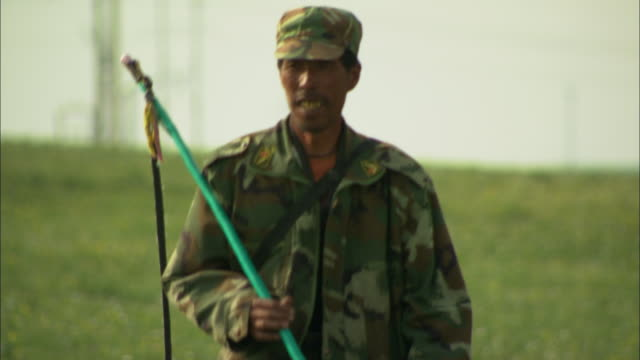 CU TD Shepherd dressed in camouflage clothing carrying whip through green field, Huitengxile, Inner Mongolia, China