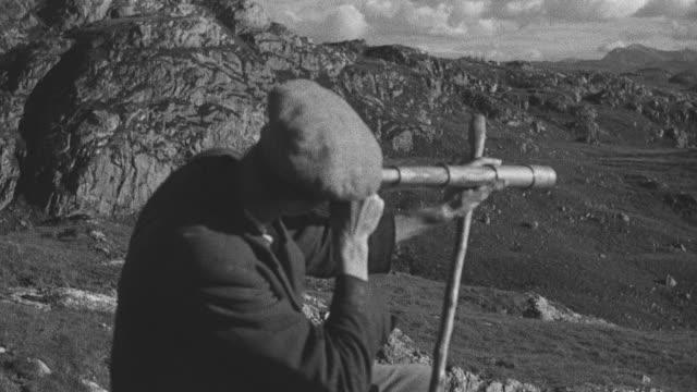 1944 MONTAGE Shepherd sitting on a remote ridge watching over his sheep through a handheld telescope / Archriesgill, Scotland, United Kingdom