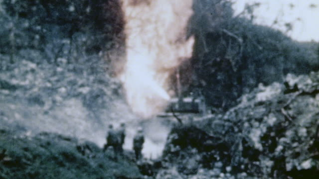 Sherman flamethrower tank burning out Japanese positions infantry mopping up and Japanese casualties where they fell / Okinawa Japan
