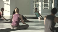MS FOCUS SHIFT_Yoga teacher instructing students in stretching, at rooftop studio