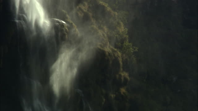 Shimmering drifting spray from waterfall pouring over rocky cliff, Madagascar