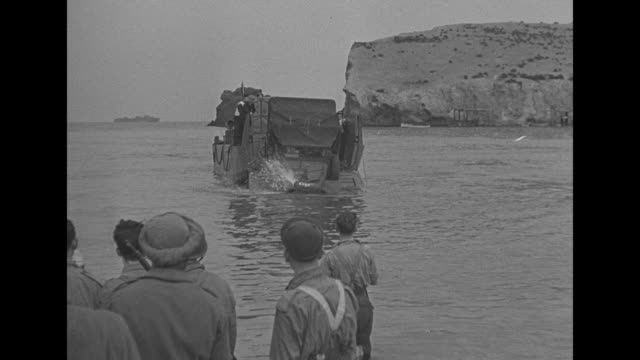 Ship anchored in African harbor with pan to arid landscape / men look on as jeep truck slowly drives into deep water / bumpy POV of man in landing...