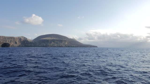 Ship cruising volcano island, San Benedicto