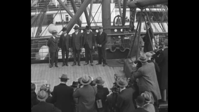 VS ship moves under American flag / high angle view of men aboard ship / cameramen crank their cameras as the US delegation to the London Naval...
