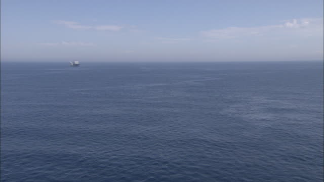 A ship travels over the expansive ocean.