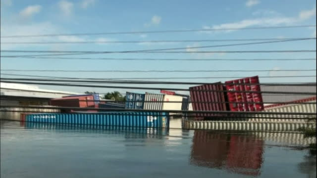 Shipping containers are tossed by flood waters in Ayutthaya Thailand
