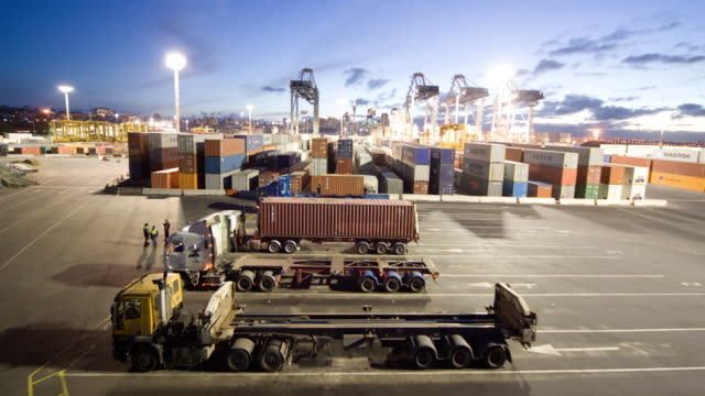 TL HA WS Shipping containers being loaded onto semi trucks at Ports of Auckland from dusk to night/ Auckland, New Zealand