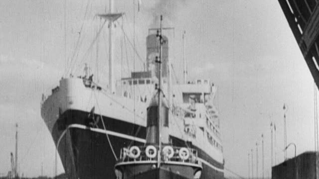 B/W Ships arriving at port and dock workers loading and unloading goods for shipping / United Kingdom