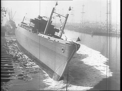 Ships at Kearny Shipyards / Miss Mary Stevenson christens destroyer with bottle of Champaign ship leaves / crowd / Mrs Horseo K Corbin swings and...