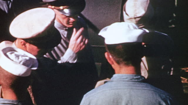 Ship's captain inspecting sailors and talking to officers on bridge of USS Monmouth County during World War II