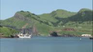 Ships moor in the Shakotan Port as vehicles drive along the coast on Shikotan Island.