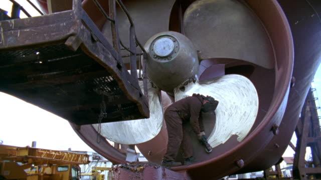 WS Shipyard worker polishing ship's propeller in dry dock, Reykjavik, Iceland