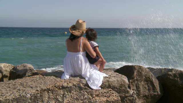 MS Shit of mother and his little girl watching waves smashing on rocks / Marbella, Andalusia, Spain