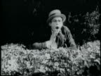 B/W 1918 shocked man in straw hat peering from behind hedge / short