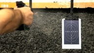 Shooting handgun pistol at target range.