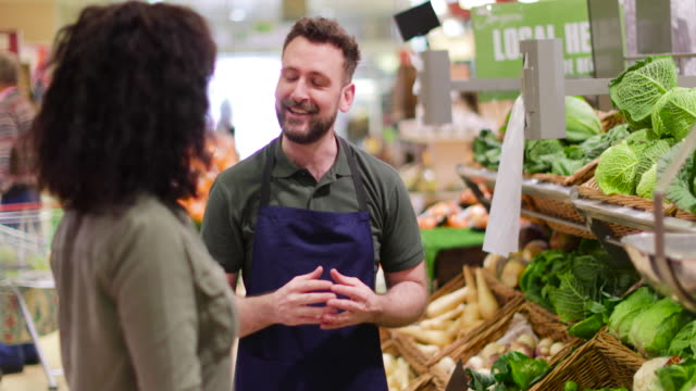 Shop assistant in grocery store helping shopper