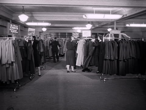 Shop assistants sort out sale items in the coat section of a department store