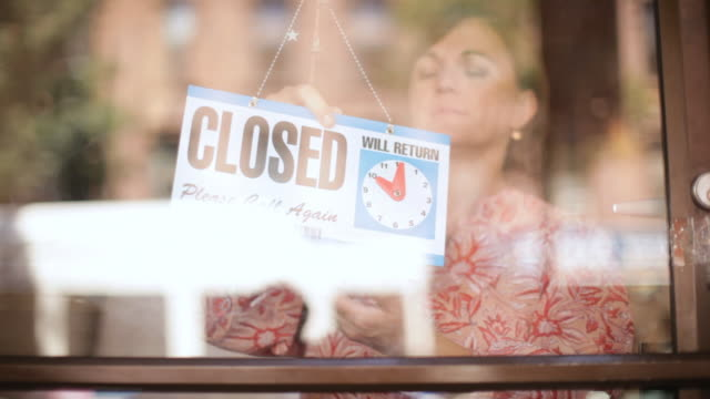MS Shop owner changing closed sign to open in store window / Brooklyn, New York, United States