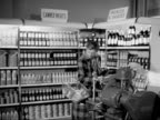 A shopper passes her ration book to a sales assistant who cuts slices of bacon for her in a selfservice store