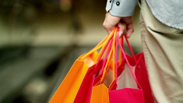 Shopper with shopping bags on escalator