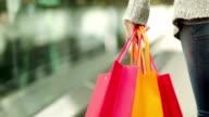 Shopper mit Einkaufstüten auf Rolltreppe