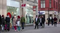 Shoppers and pedestrians walk past a Hennes Mauritz AB fashion store on Market Street in Manchester city centre Retail in Manchester city centre on...