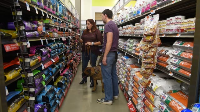 Shoppers browse pet products inside a Petco store in New Jersey US on September 2 2015 Shots Various shots of customers walking through aisles inside...