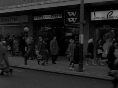 Shoppers mover along a busy high street in Liverpool 1964