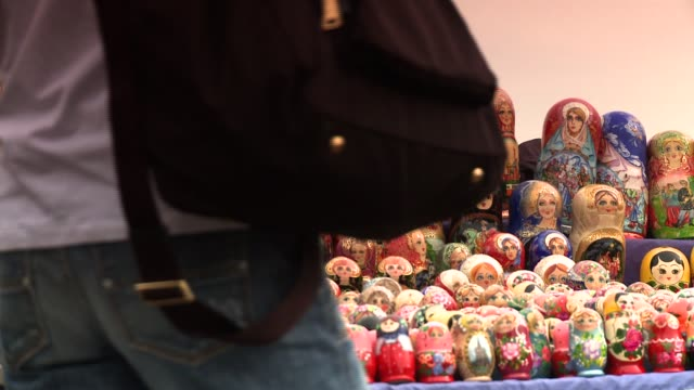 Shoppers pass a display of Matryoshka dolls. Available in HD.