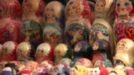 Shoppers pass a table loaded with Matryoshka dolls. Available in HD.