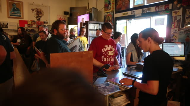 Shoppers pay for their purchases at Landlocked Records during Record Store Day April 16 2016 in Bloomington Indiana Record Store day was created to...