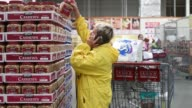 Shoppers push carts through a Costco Wholesale Corp store in East Peoria Illinois US on Tuesday May 26 2015 Shots an employee demonstrates a Vitamix...