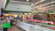 Shoppers selecting items from the freezer section of a warehouse store.