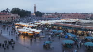 Shoppers walk past food and merchandise booths at the Djemaa el-Fna market in Marrakesh, Morocco.