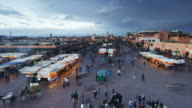 Shoppers walk past food and merchandise booths in the Djemaa el-Fna night market in Marrakesh, Morocco.