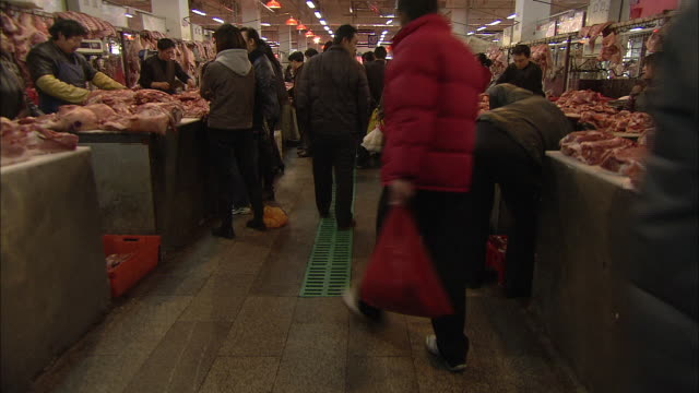 Shoppers walk through a busy meat market in China.