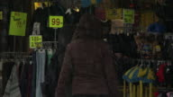Shoppers wear hooded coats as they shop for sales in the rain.