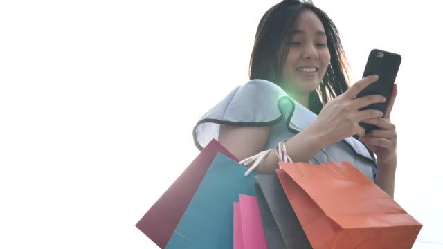 Asiatische Frau hält einen Smartphone und Kreditkarte einkaufen
