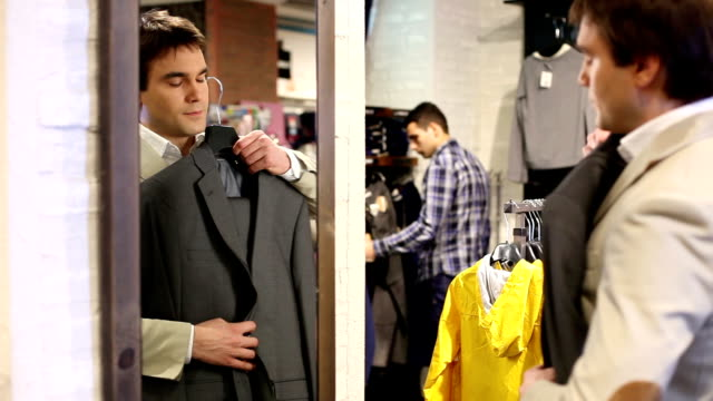 Shopping man in front of a mirror holding suit