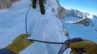 POV Short roped mountaineers walking over snowy ridge in sunshine