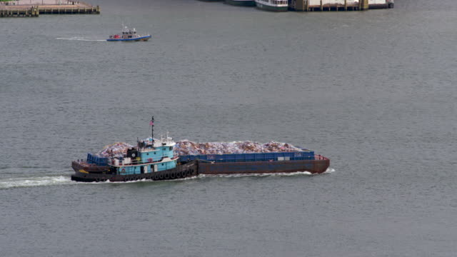 Shot follows a trash barge being pushed by a tugboat down the Hudson River