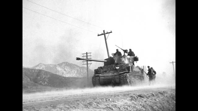 Shot from behind soldiers of three US tanks in row in field / shot from below of tank on road on top of embankment three soldiers standing behind it...