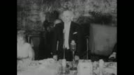 Shot from behind two cameramen shooting footage of Presidential Electors Association dinner / reelected President Harry Truman standing at head table...