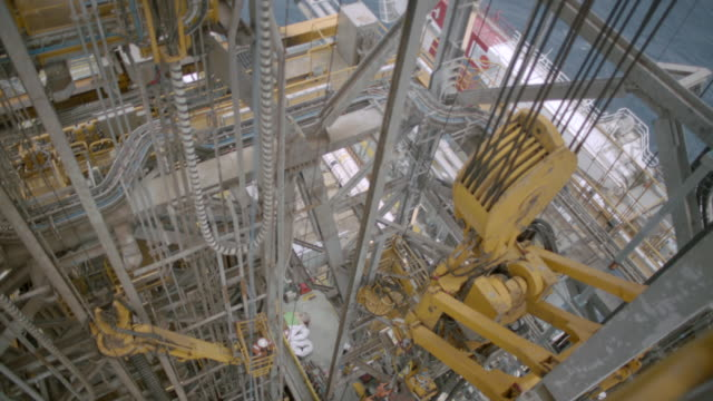 WS TU Shot from high up showing moving machinery below Then follows large piece until it reaches top Oil rig in / The North Sea