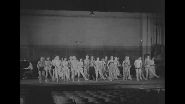 Shot from out in audience seats of chorus girls on stage practicing dance routine / Note exact month/day not known