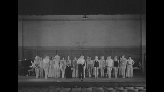 Shot from out in audience seats of George White writer producer and director of show 'Scandals' standing in front of chorus girls on stage giving...