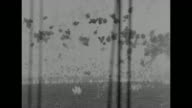 Shot from ship of Japanese plane diving through flak catching fire and crashing into ocean two ships in foreground / shot from ship of Japanese plane...