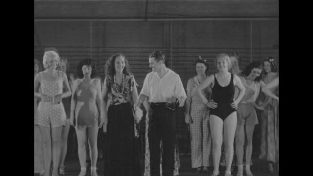 Shot from stage level of George White writer producer and director of show standing in front of chorus girls giving them directions he leads them in...