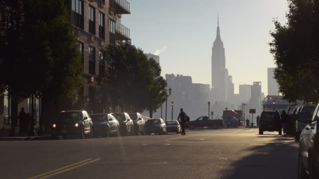 Shot from the street of people walking on a street with the Empire State Building and the Manhattan Skyline in the background
