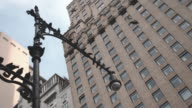 POV shot looking up at pigeons on a New York City lamp post
